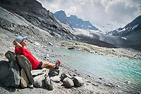 A woman trail runner reclines on a stone bench next to a small mountain lake, Val de Bagnes, Switzerland.
