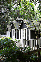 The summer cabins in the garden are built on wooden piles