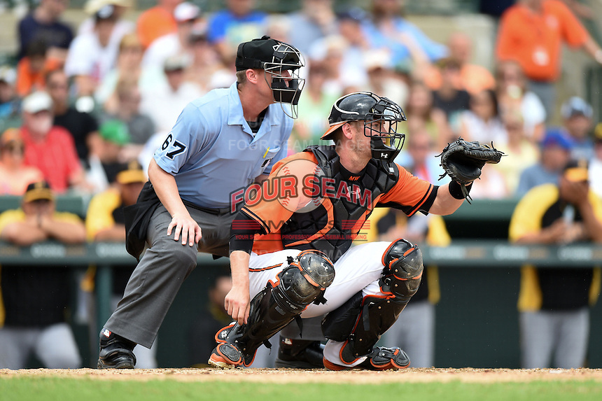 Umpire Seth Buckminster and Baltimore Orioles catcher Matt Wieters (32) during a spring training game against the Pittsburgh Pirates on March 23, 2014 at Ed Smith Stadium in Sarasota, Florida.  Baltimore and Pittsburgh tied 7-7.  (Mike Janes/Four Seam Images)