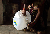 Rani Barukaum, the local SHG leader speaks pours water out of the iJal can in Ambedkar Nagar in Medak, Telangana, India.