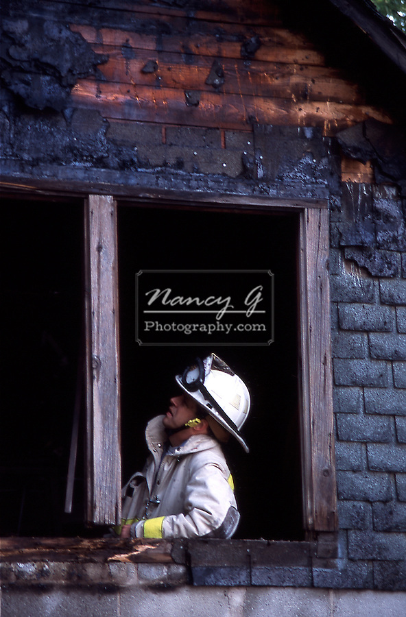 A fire fighter investigating fire evidence in a burnt window frame