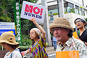 """Tokyo, Japan - June 17: In front of a sign, """"No Nuclear Power and Peace Are The Wish of Everyone,"""" people marched against nuclear power plants in Japan at Mitaka, Tokyo, Japan on June 17, 2012. As Japanese Government decided to restart Oi Nuclear Power Plants No.3 and 4 in Fukui, people spoke up against the restart throughout the nation. ."""