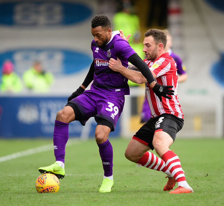 Grimsby Town's Wes Thomas shields the ball from Lincoln City's Neal Eardley<br /> <br /> Photographer Chris Vaughan/CameraSport<br /> <br /> The EFL Sky Bet League Two - Lincoln City v Grimsby Town - Saturday 19 January 2019 - Sincil Bank - Lincoln<br /> <br /> World Copyright &copy; 2019 CameraSport. All rights reserved. 43 Linden Ave. Countesthorpe. Leicester. England. LE8 5PG - Tel: +44 (0) 116 277 4147 - admin@camerasport.com - www.camerasport.com