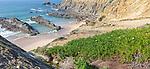 Rocky coastal landscape Praia dos Alteirinhos beach in bay with rocky headland part of Parque Natural do Sudoeste Alentejano e Costa Vicentina, Costa Vicentina and south west Alentejo natural park, Zambujeira do Mar, Alentejo  Littoral, Portugal, southern Europe