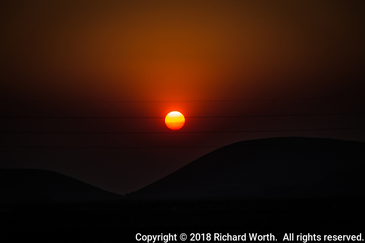 The sun glows in skies filled with smoke from wildfires north of the San Francisco Bay area.  Near the Coyote Hills Regional Park, Fremont, California.