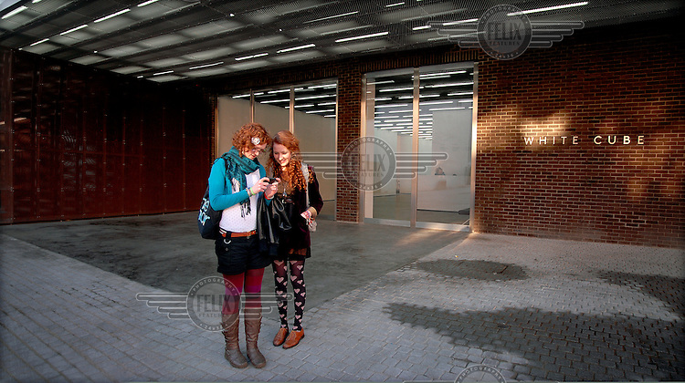 Young women check a mobile phone outside the White Cube Art Gallery on Bermondsey Street in London.
