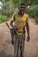 Bangladesh, Jhenaidah. Man climbing tree to collect date juice.