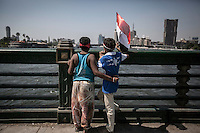 In this Friday, Jul. 26, 2013 photo, two kids watch an army helicopter rounding over Nilo river in the nearby brigde of Tahrir square in Cairo. (Photo/Narciso Contreras).