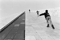 "Albania. Tirana. Three teenagers run up the slopes of the Pyramid to get to the top of the building. The Pyramid, also called International Center of Culture, is a structure and former museum that opened on October 14, 1988, formerly known as the ""Enver Hoxha Museum"". Its angled shape structure vaguely reminiscent of a pyramid was designed by the daughter and son-in-law of the late communist leader Enver Hoxha. It was originally intended to be a mausoleum and museum for the country's deceased leader Enver Hoxha. It served as a museum about his legacy. Then came in 1991 the collapse of communism. Albania's transition from isolated Stalinist state to aspiring member of the EU has been reflected in the fortunes of Tirana's pyramid. In 1991, the building was renamed in honor of persecuted activist Pjeter Arbnori and became a conference center and exhibition venue. During the 1999 conflict in Kosovo, NATO set up a humanitarian headquarters inside the pyramid. In 2001, Albanian television station Top Channel moved in. In 2010, the Albanian government decided to raze the pyramid and build a sleek new parliament building in its place. The pyramid, however, still stands. Though many would like to destroy the specter of communist rule, a vociferous group Albanian intellectuals, activists, and even former political prisoners of Hoxha are in favor of its preservation. Ther argument: history, no matter how dark or ugly, must be remembered. As debate continues (2016), the pyramid sits dilapidated and vandalized, awaiting an uncertain future. Tirana is the capital and largest city of Republic of Albania. 24.11.1998 © 1998 Didier Ruef"