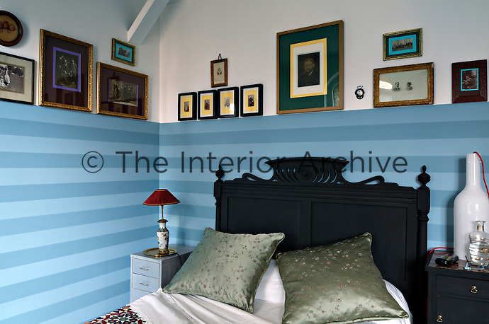 The black-painted headboard is in dramatic contrast to the blue striped walls of this niche bedroom, which is lined with antique family photographs