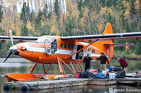 Group of people packing up a float plane for a fly-in fishing trip.