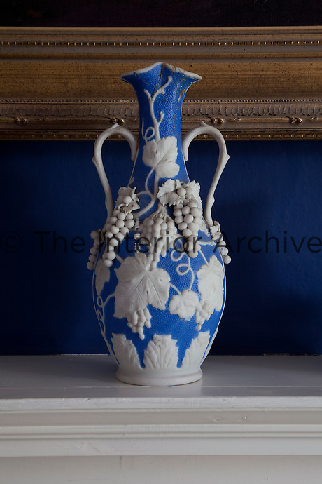 A sculptural blue and white vase, bulging with grape vines on the mantelpiece in the dining room