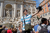 Rome continue to be one of the most visited city in the world..Roma continua ad essere una delle città più visitata al mondo.A japanese tourist takes a self portrait at the Trevi fountain