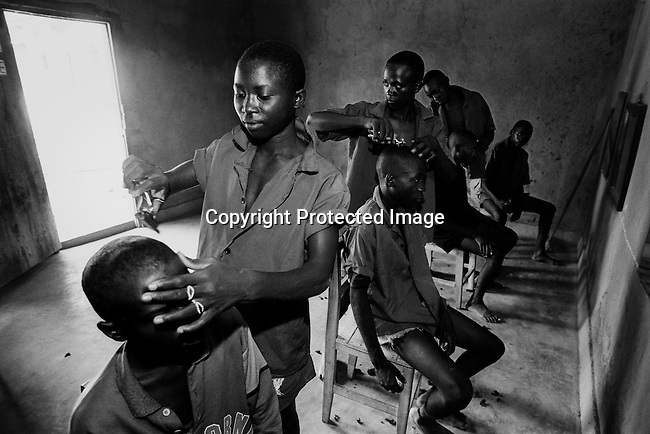 Youth prisoners accused of the genocide in Rwanda in 1994, cut hair on each other in a youth prison on April 20, 1995 in Gitagata, Rwanda. About one million people were killed in about one hundred days, making it one of the worst Genocides in modern history. (Photo by:Per-Anders Pettersson)