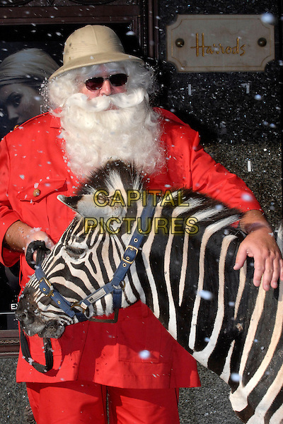 "SANTA CLAUS .At the opening of ""Christmas World"" at Harrods, London, UK. .August 8th, 2006.Ref: FIN.half length hat zebra animal safari red striped stripes sunglasses shades.www.capitalpictures.com.sales@capitalpictures.com.©Steve Finn/Capital Pictures."