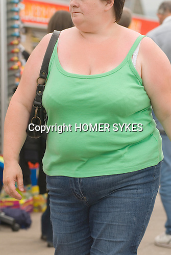Ordinary fat young woman on holiday Wales wearing green T shirt and blue jeans.  UK 2008.