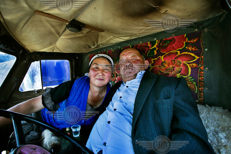 A couple attending the weekly animal market drinking vodka in their truck.