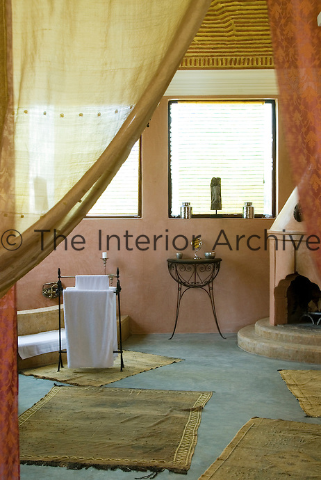 Thin rugs cover the concrete floor of one of the bathrooms at Le Palais Rhou in Marrakech