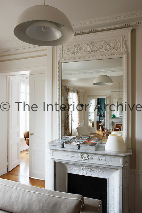 In the more informal living room adjacent to the the drawing room magazines are stacked in piles on the antique marble mantelpiece