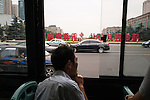 A man enjoys the cool morning breeze on a bus in the new part of Qingdao. In the distance visible is the new symbol of Qingdao – a flame. Qingdao hosted the sailing championships of the Olympic Summergames in 2008.