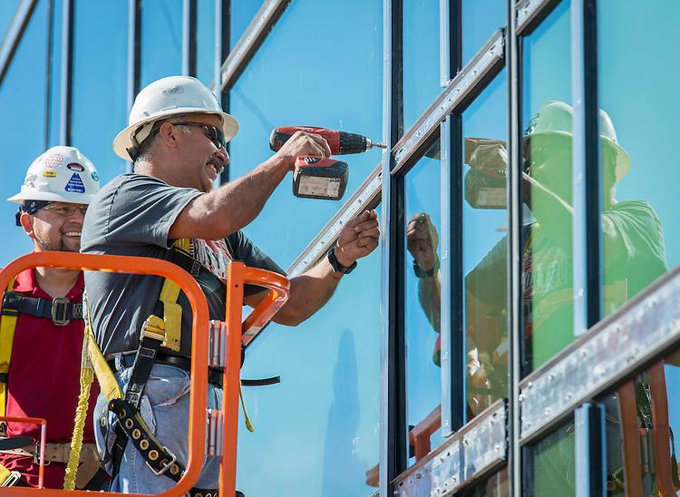 Workmen install windows at Waltrip High School, January 28, 2015.
