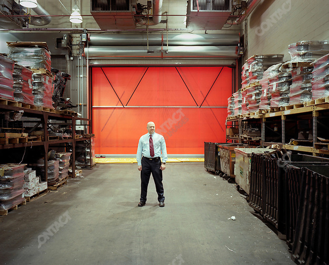 """Doug Luback, of the Department of Sanitation, stands in front of a newly installed """"quick roll up door,"""" an automatic device which is purported to save much more energy than the previously remote-controlled metal versions. New York City, New York, March 20, 2009"""
