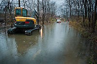 Construction equipment sits  in flood waters along a bike path under Schrock Road in Westerville. The equipment is used by the crew building a flood  retaining wall to keep flood waters from Alum Creek overflowing its banks and covering the bike path. The wall has yet tobe completed.