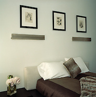 In the guest bedroom three monochrome prints in black frames are arranged above a pair of matching metal striplights