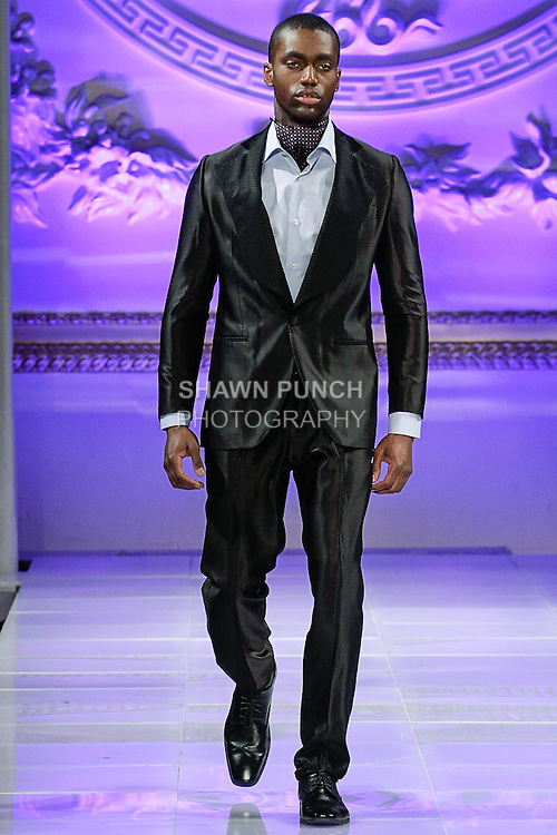Model walks runway in a suit from the Dianthusd'kangala collection by Allex Kangala, during Couture Fashion Week New York Fall 2013, on February 17, 2013.