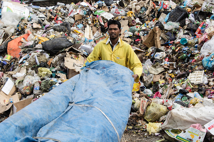 10/10/2014 -- Kirkuk, Iraq -- A Balgladeshi worker trows away the trash after cleaning the streets.