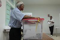 23 ottobre 2011 Tunisi, elezioni libere per l'Assemblea Costituente, le prime della Primavera araba: uno scrutinatore nel seggio appoggiato sull'urna elettorale. Sullo sfondo una donna piega la scheda elettorale.October 23, 2011 Tunis, free elections for the Constituent Assembly, the first of the Arab Spring: a representative in the polling station election. In the background a woman folds the ballot.<br /> <br /> premieres elections libres en Tunisie octobre <br /> tunisian elections