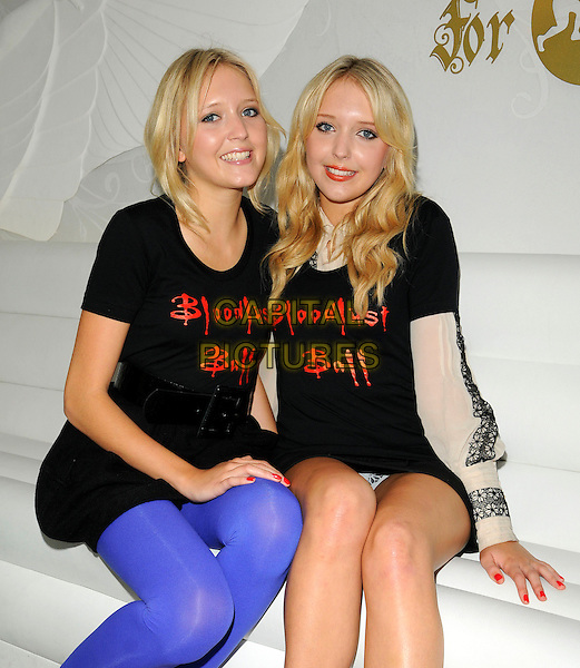 SAMANTHA & AMANDA MARCHANT.Bloodlust Photocall to promote the forthcoming Bloodlust Ball and to promote the Blood Donor scheme, at Vendome, Piccadilly, London, England, UK..October 15th 2008.half length sitting twins big brother Sam black t-shirt slogan samanda sisters siblings blue purple leggings tights flashing knickers underwear 3/4.CAP/CAN.©Can Nguyen/Capital Pictures.