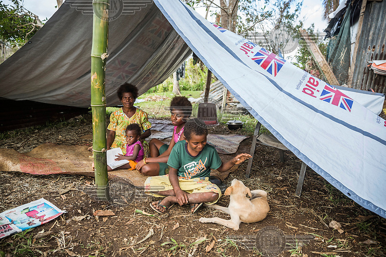 10 year old James with his mother Margaret, his three year old sister, Ester, 14 year old sister Pricilla and their dog Snoopy, all sitting beneath an improvised tent, provided them as part of an international emergency aid effort in response to the destruction wrought by Cyclone Pam on 13 March 2015.