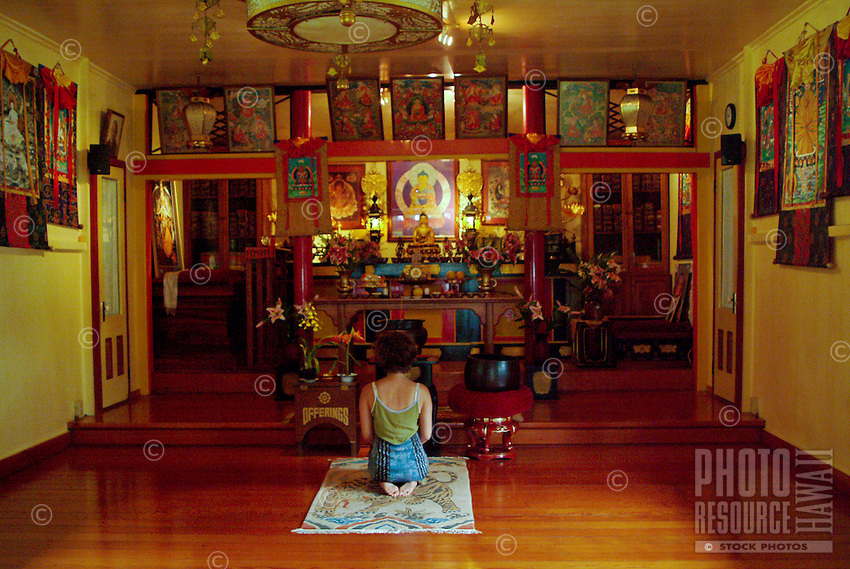 Young woman age 21 kneeling at the beautiful golden Buddhist wood valley temple altar on the Kau south end of the Big island of Hawaii