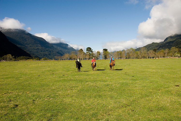 Chile, Lake Country: People riding horses at Peulla in a meadow in the Andes..Photo #: ch606-33246..Photo copyright Lee Foster www.fostertravel.com, lee@fostertravel.com, 510-549-2202.