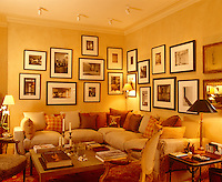A corner sofa, scatter cushions and subdued lighting have resulted in this intimate space where a collection of black and white photographs is displayed on the adjacent walls