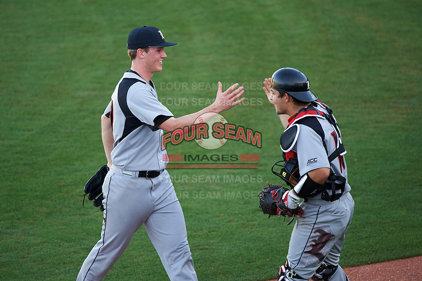 Louisville Cardinals relief pitcher Riley Thompson (32) and catcher Zeke Pinkham (11) shake hands in between innings during a game against the Ball State Cardinals on February 19, 2017 at Spectrum Field in Clearwater, Florida.  Louisville defeated Ball State 10-4.  (Mike Janes/Four Seam Images)