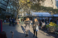 Visitors to Bryant Park in New York enjoy the unseasonable warm weather while shopping at the Bryant Park Holiday Market, looking for Christmas gifts, on Monday, November 16, 2015. (© Richard B. Levine)
