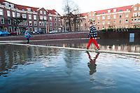 Nederland, Rotterdam, 2 jan 2013.Bellamyplein in de wijk Spangen is heringericht mede om het regenwater beter op te vangen. Bij veel regen, wat de laatste dagen zo was, loopt de kuil op het plein vol water. Zo raakt het riool niet overbelast.  Voor kinderen is het een leuke speelplek..Foto(c): Michiel Wijnbergh