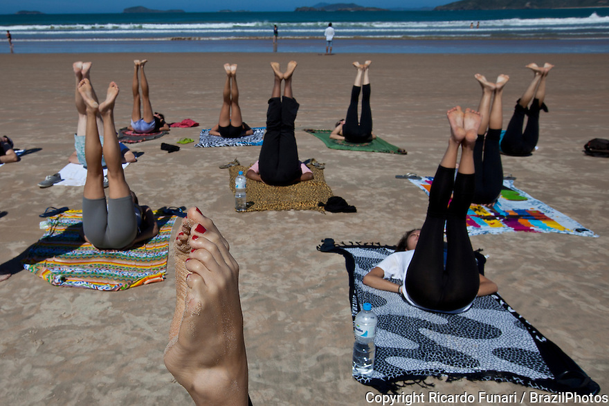 Young people practicing yoga at Geriba beach, Armacao de Buzios, Rio de Janeiro State, Brazil - physical, mental, and spiritual practice with a view to attain a state of peace and wellness.