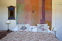 Pretty embroidered cushions and bedlinen with a floral motif have been juxtaposed with a vintage patchwork wall hanging in a guest bedroom