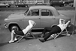 Southend-on-Sea, Essex. 1974<br /> A middle-aged couple with their Austin Cambridge A50 and own deck chairs enjoy a sleepy Saturday afternoon in sun.