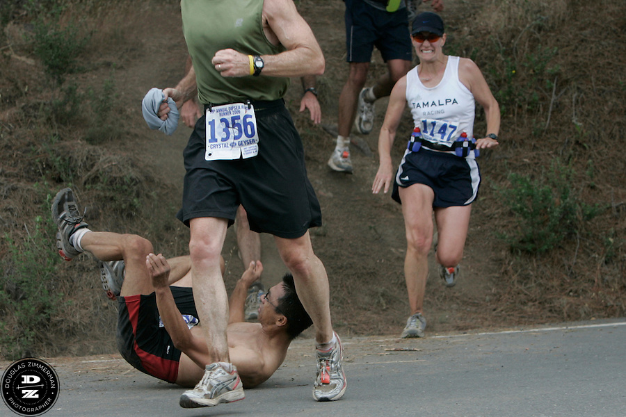 Mike Peng (1302) of Irvine falls after leaping off the trail and onto Highway 1 as (1147)  Jenniger Lanciault of Corte Madera looks on.  The leap onto Highway 1 in Stinson Beach is the last part of the dirt trails in the race and leads to the final quarter-mile of the race to the finish line.  The 99th running of the Dipsea Race finished at Sintson Beach State Park in Stinson Beach, Calif. on Sunday June 14th, 2009.
