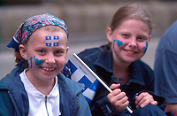 June 23 2002, Montreal, Quebec, Canada<br /> <br /> Quebecer of all origin , many of them displying Quebec flags,<br /> wait for the<br /> St Jean baptist ( Quebec national Holliday)<br />  Parade, June 23 2002 on Notre Dame Street in Montreal Canada.<br /> <br /> Festivities continue tomorrow June 24, which the actual date of the St Jean Baptiste.<br /> <br /> Mandatory Credit: Photo by Pierre Roussel- Images Distribution. (©) Copyright 2002 by Pierre Roussel <br /> <br /> NOTE :l Nikon D-1 jpeg opened with Qimage icc profile, saved in Adobe 1998 RGB.<br /> This photo is also available in the original size, with less compression (TIFF or JPEG 12)
