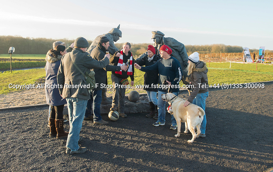 """25/12/14<br /> <br /> Football fans from around the world kick a football around and pay their respects by a sculpture depicting two WW1 soldiers playing football during the famous Christmas Day truce in the field near Messine, Belgium, close to where the match was played in Flanders, Belgium.<br /> <br /> The sculpture, made in England, arrived in Flanders on Christmas Eve, and was first displayed in the town centre before being taken to the spot where the match was played. <br /> <br /> Sculpted by Andy Edwards the work is entitled 'All Together Now', recalling the song by the band The Farm - which was inspired by the truce. <br /> <br /> Chris Butler said: """"Castle Fine Arts are proud to have cast a number of war memorials over the years. We are honoured to support this sculpture for peace. I believe it will touch the hearts of millions.""""<br /> <br /> <br /> """"It will be a symbol of peace and hope and a call for a renewed worldwide cessation of violence in honour of those brave boys who 'joined together and decided not to fight'"""".<br /> <br /> <br /> The statue depicts the meeting of a British and a German soldier over a football, deep in the mud between the lines on that first Christmas of the war. The soldiers appear to be shaking hands but  are not not quite touching, forming a space in which a visitor can insert their own hand to complete the union.  A chance for a moments reflection on how far we are from true peace and brotherhood and the part each of us has to play in that dream. We want the work to stand as both a celebration of this inspirational and heroic event and as symbol of hope and peace. <br /> <br /> The project was instigated some years ago, with the support of the Football Asscociation (FA), as football's contribution to the First World War commemorations. <br /> <br /> All Rights Reserved - F Stop Press. www.fstoppress.com. Tel: +44 (0)1335 300098"""