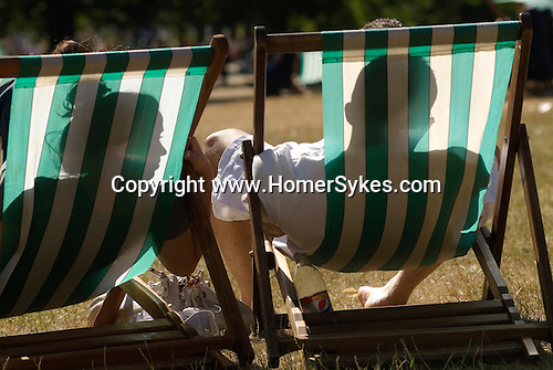 Heat wave hot weather couple deckchairs Hyde Park London Uk 2010.