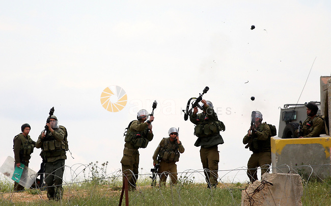 Israeli soldiers fire tear gas canisters toward protesters during the weekly demonstration against Israel's controversial separation barrier in the village of Bilin, near the West Bank city of Ramallah on April 22, 2011. Some 250 left-wing Israeli and foreign activists protested in the West Bank village of Bilin against the separation fence being built in the area. Some of the protestors hurled stones at the security forces, who used crowd dispersal means in response. Photo by Issam Rimawi