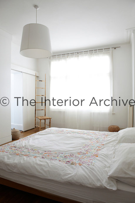 A white bedroom with a sheer curtain at the window and a double bed with an embroidered duvet cover.