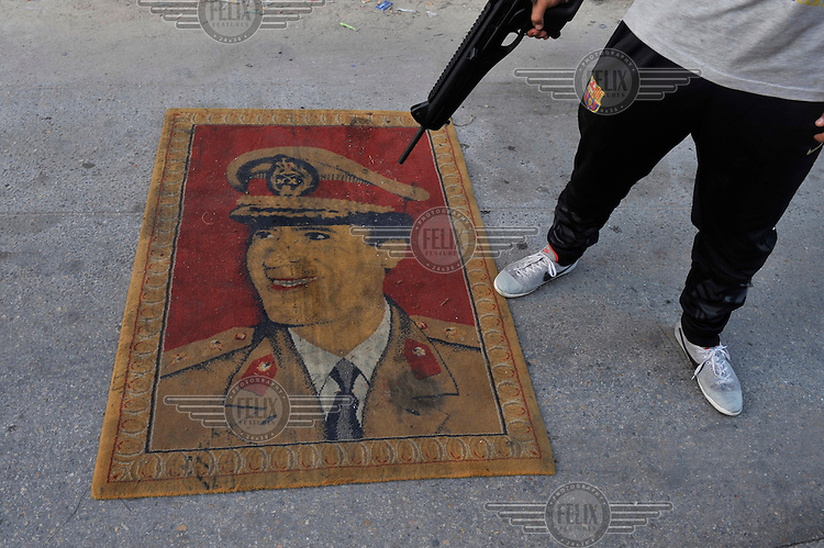 A man points a gun at a carpet which has a picture of Gaddafi on it, lying on a street in Tripoli. After a six month revolution, rebel forces finally managed to break into Tripoli and have taken control of Bab al-Aziziyah, Col Gaddafi's compound and residence. Few remain that are loyal to Gaddafi in the city; it is seeming that the 42 year regime has come to an end. Gaddafi is currently on the run.