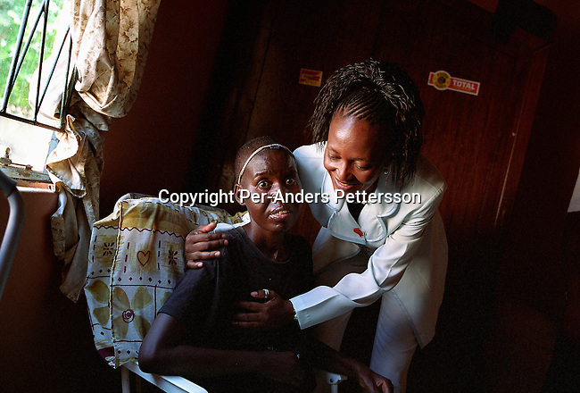 GABORONE, BOTSWANA - FEBRUARY 28: Cynthia Leshomo, age 32, the winner in the Miss HIV Stigma Free Botswana contest, visits and comforts a woman suffering from HIV-Aids in her home a few days after she won the title on February 28, 2005 in Gaborone, Botswana. The pageant is held to make the people of Botswana more aware of HIV-Aids, and stop the stigma that makes people afraid of being tested. Botswana has a population of about 1,7 million people and about 38 percent are believed to be infected with the virus. Cynthia impressed the jury with her mix of beauty and brains and won the competition. She lives with HIV and takes antiretroviral drugs two times a day. .(Photo: Per-Anders Pettersson/Getty Images)